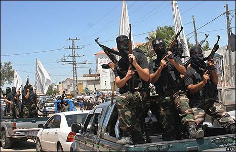 Hamas militants stand with rifles on the back of a pickup in convoy during a funeral in Gaza City